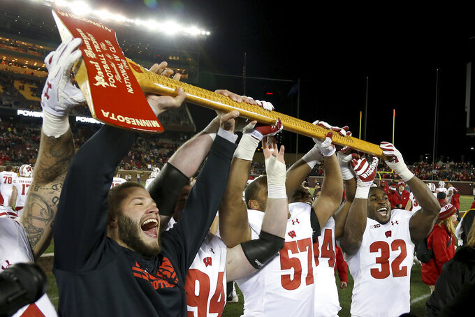 FILE - In this Nov. 25, 2017, file photo, Wisconsin players hold up Paul Bunyan's Axe up after winning 31-0 against Minnesota in an NCAA college football game, in Minneapolis. The last week of the regular season in the Big Ten means a slate of rivalry games. Barry Alvarez was pacing the sideline as coach the last time that Wisconsin lost Paul Bunyan's Axe to Minnesota. It was 2003, but the empty feeling that comes with losing the rivalry game remains fresh. Losing stings.(AP Photo/Stacy Bengs, File)