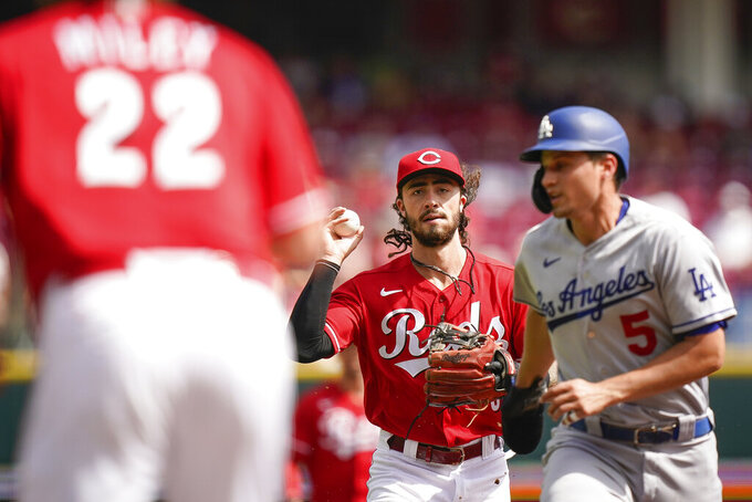 Cincinnati Reds third baseman Jonathan India (6) and starting pitcher Wade Miley (22) catch Los Angeles Dodgers' Corey Seager (5) in a run down between first and second base during the second inning of a baseball game in Cincinnati, Sunday, Sept 19, 2021. (AP Photo/Bryan Woolston)