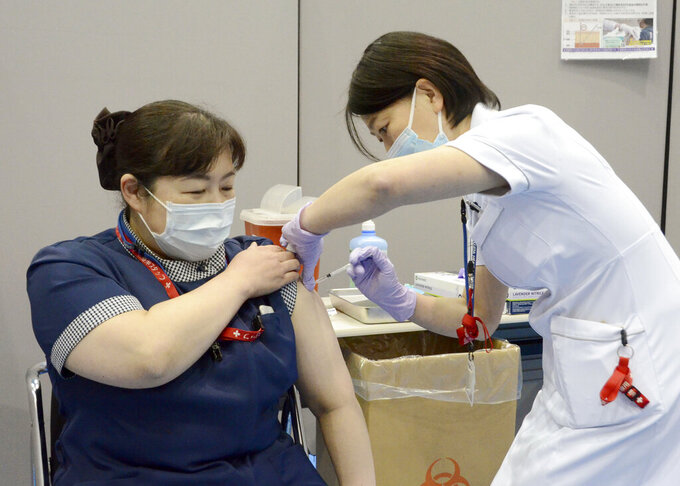 A nurse receives the first dose of the Pfizer COVID-19 vaccine at Fujita Health University Hospital in Toyoake, Aichi prefecture, central Japan, on March 8, 2021. Some nurses in Japan are incensed at a request from Tokyo Olympic organizers to have 500 of them dispatched to help out with the games. They say they're already near the breaking point dealing with the coronavirus pandemic.  (Kyodo News via AP)