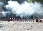 Iraqi security forces fire tear gas to disperse anti-government protesters during a demonstration in central Baghdad, Iraq, Friday, Oct. 25, 2019. Iraqi police are firing tear gas to disperse thousands of protesters in Baghdad where planned anti-government demonstrations have resumed after a three-week hiatus. (AP Photo/Hadi Mizban)