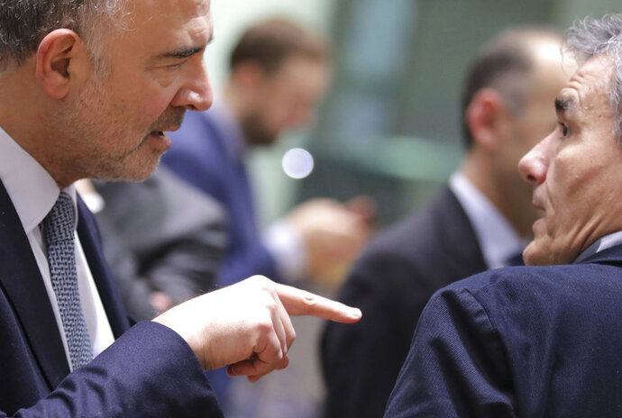 European Commissioner for Economic and Financial Affairs Pierre Moscovici, left, speaks with Greek Finance Minister Euclid Tsakalotos during a round table meeting of eurogroup finance ministers at the Europa building in Brussels, Monday, Dec. 3, 2018. Eurozone finance ministers meet in Brussels on Monday to discuss the standoff between Italy and the group over its spending proposals for the 2019 budget. (AP Photo/Olivier Matthys)