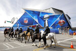 Police on horseback patrol past Mercedes-Benz Stadium ahead of Sunday's NFL Super Bowl 53 football game between the Los Angeles Rams and New England Patriots in Atlanta, Wednesday, Jan. 30, 2019. (AP Photo/David Goldman)