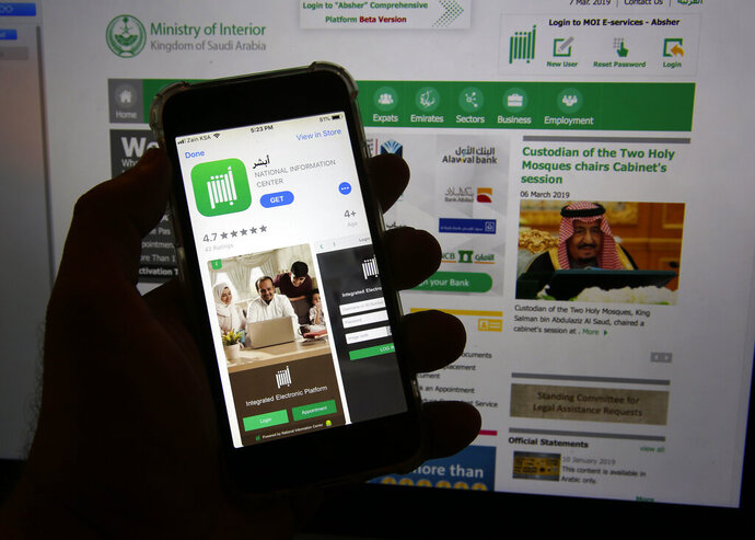 This photo shows the Absher App on a phone in Jiddah, Saudi Arabia, Thursday, March 7, 2019. The Saudi government app is mostly a way for people to pay traffic fines and complete other administrative tasks electronically. But one feature isn't sitting well with civil-rights advocates: the ability for men to grant or deny a woman permission to travel. (AP Photo/Amr Nabil)