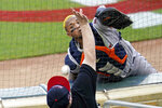 Houston Astros catcher Martin Maldonado, top, makes a try for a foul ball off the bat of Minnesota Twins' Josh Donaldson but it went inside the mesh fencing by a fan in the first inning of a baseball game, Friday, June 11, 2021, in Minneapolis. (AP Photo/Jim Mone)