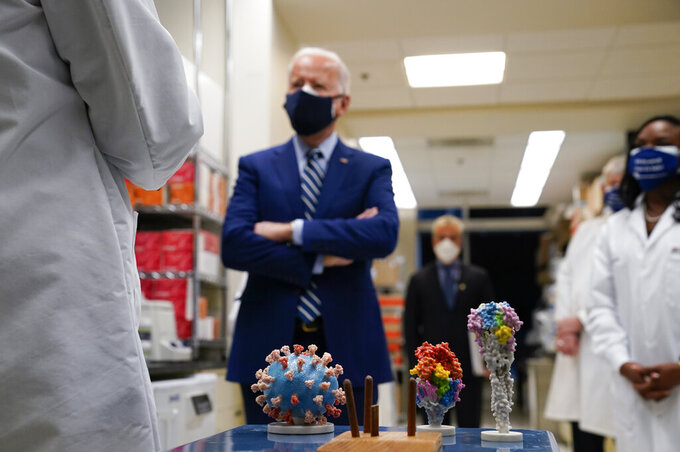 FILE - In this Thursday, Feb. 11, 2021 file photo, President Joe Biden visits the Viral Pathogenesis Laboratory at the National Institutes of Health (NIH) in Bethesda, Md. At bottom center is a model of the COVID-19 virus. On Friday, Feb. 26, 2021, The Associated Press reported on stories circulating online incorrectly asserting Biden restored taxpayer funding for the Wuhan Institute of Virology. Social media usersare falsely claiming the Biden administration is bankrolling the Wuhan Institute of Virology, a Chinese lab which has faced unproven allegations that the coronavirus leaked from the facility leading to the global COVID-19 pandemic. (AP Photo/Evan Vucci)