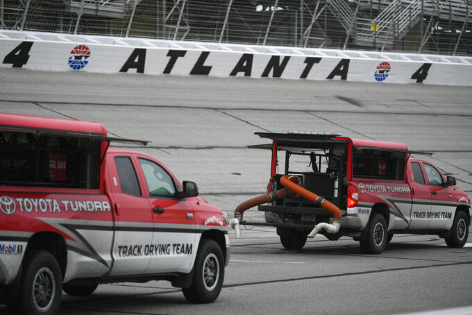 Trucks attempt to dry the track before practice and after qualifying was cancelled before a NASCAR XFINITY auto race at Atlanta Motor Speedway, Saturday, Feb. 23, 2019, in Hampton, Ga. (AP Photo/John Amis)