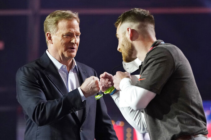 NFL Commissioner Roger Goodell, left, fist-bumps Cleveland Browns coach of the year Marty Gibbons, from Lake Catholic High School, before Gibbons announces the Browns second round draft pick of the NFL football draft, Friday, April 30, 2021, in Cleveland. The Browns picked Jeremiah Owusu-Koramoah, linebacker for Notre Dame. (AP Photo/Tony Dejak)