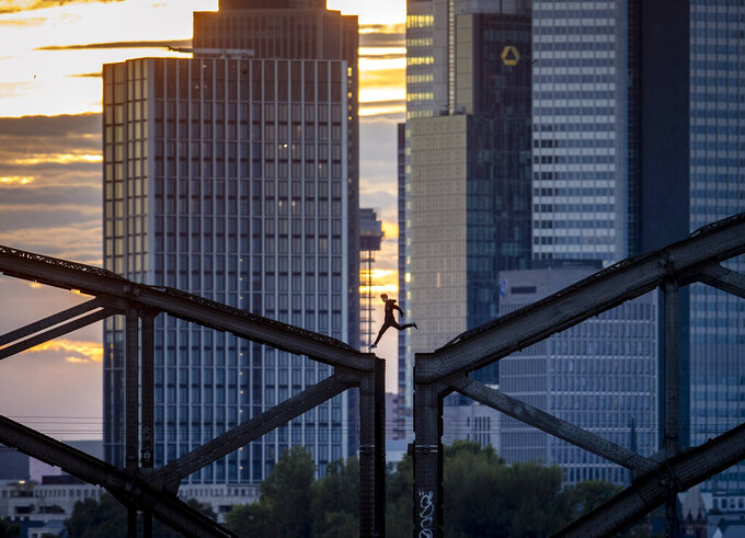 A parkour runner jumps on a railway bridge with the buildings of the banking district in background in Frankfurt, Germany, on Sept. 9, 2020. (AP Photo/Michael Probst)