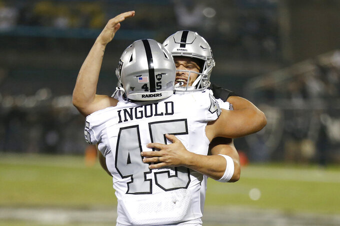Oakland Raiders running back Alec Ingold (45) celebrates with quarterback Derek Carr after they connected on a touchdown pass against the Los Angeles Chargers during the first half of an NFL football game in Oakland, Calif., Thursday, Nov. 7, 2019. (AP Photo/D. Ross Cameron)