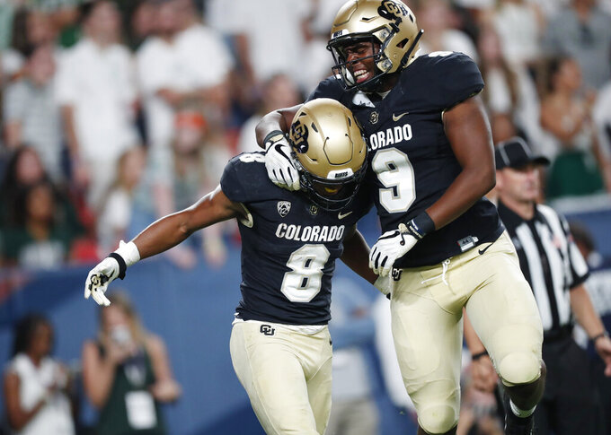 Colorado tight end Jalen Harris, right, celebrates with running back Alex Fontenot, who scored a touchdown against Colorado State in the third quarter of an NCAA college football game Friday, Aug. 30, 2019, in Denver. (AP Photo/David Zalubowski)