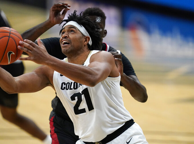 Colorado forward Evan Battey, front, drives to the net past Omaha forward Wanjang Tut in the second half of an NCAA college basketball game Wednesday, Dec. 16, 2020, in Boulder, Colo. Colorado won 91-49. (AP Photo/David Zalubowski)
