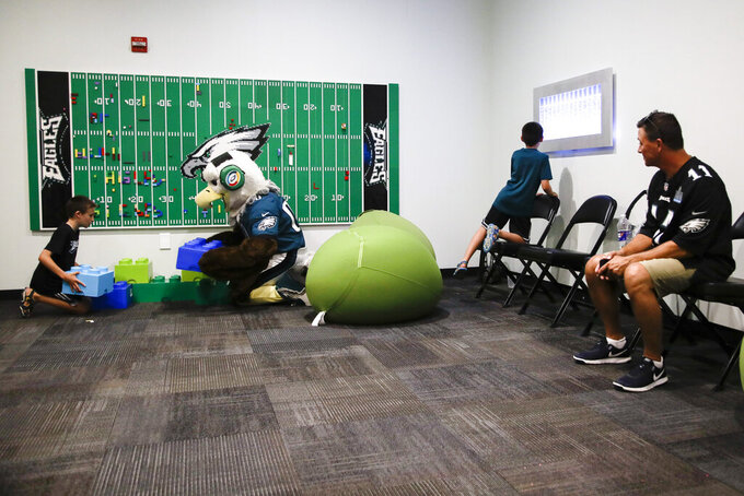 In this Thursday, Aug. 22, 2019, photo, Victor Ykoruk, right, watches as his 10-year-old twin sons, Ryan, left, and Jack, play in the Lincoln Financial Field sensory room, before a preseason NFL football game between the Philadelphia Eagles and the Baltimore Ravens in Philadelphia. The Eagles partnered with Children's Hospital of Philadelphia and nonprofit KultureCity in the offseason to build a state-of-the-art sensory room on a suites level inside the Linc to accommodate fans and families managing sensory challenges. (AP Photo/Matt Rourke)