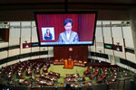 """A TV screen shows Hong Kong Chief Executive Carrie Lam delivering her policies at chamber of the Legislative Council in Hong Kong, Wednesday, Nov. 25, 2020. Lam said Wednesday that the city's new national security law has been """"remarkably effective in restoring stability"""" after months of political unrest, and that bringing normalcy back to the political system is an urgent priority. (AP Photo/Kin Cheung)"""