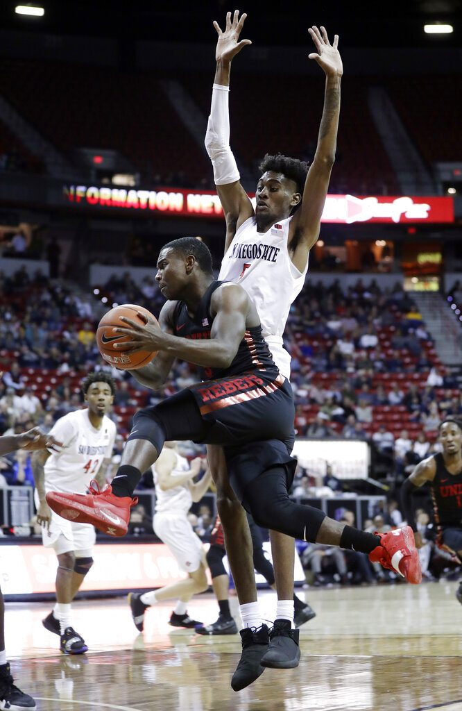 San Diego State's Jalen McDaniels defends as UNLV's Amauri Hardy drives to the basket during the second half of an NCAA college basketball game in the Mountain West Conference men's tournament Thursday, March 14, 2019, in Las Vegas. (AP Photo/Isaac Brekken)