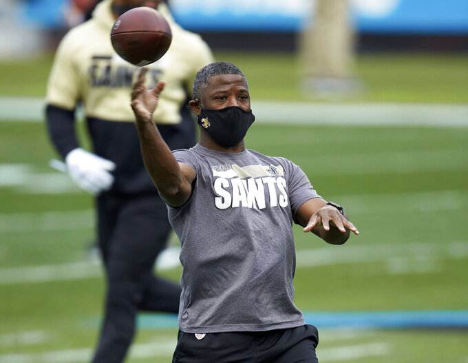FILE - In this Jan. 3, 2021, file photo, New Orleans Saints secondary coach Aaron Glenn throws prior to an NFL football game against the Carolina Panthers in Charlotte, N.C. The New York Jets interviewed Tennessee Titans offensive coordinator Arthur Smith and Glenn on Monday, Jan. 11, 2021, for their head coaching vacancy. (AP Photo/Brian Westerholt, File)