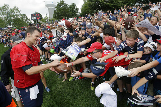 FILE - In this Aug. 3, 2017, file photo, New England Patriots' Tom Brady, left, signs autographs for fans at NFL football training camp in Foxborough, Mass. Tom Brady is an NFL free agent for the first time in his career.  The 42-year-old quarterback with six Super Bowl rings  said Tuesday morning, March 17, 2020, that he is leaving the New England Patriots. (AP Photo/Steven Senne)