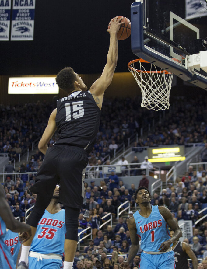 Nevada forward Trey Porter (15) dunks the ball against New Mexico in the first half of an NCAA college basketball game in Reno, Nev., Saturday, Feb. 9, 2019. (AP Photo/Tom R. Smedes)