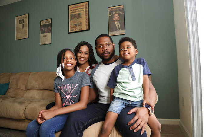 In this Tuesday, June 16, 2020 photo, D.J. Boldin, second from right, poses for a photograph with his children Madison, 10, left, and Dallas, 4, right, and his fiancee Sasha Jones at their home in Miramar, Fla. Boldin is the football coach at Pahokee High School, a predominantly black school located alongside Lake Okeechobee in Florida. Recent events have given Boldin an opportunity to use his position to prepare his players for the challenges they will face when they leave the bubble that is their small town. (AP Photo/Lynne Sladky)