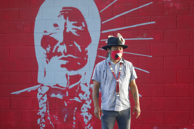 Native American advocate Carl Moore stands in front of a mural of an Indigenous man meant to represent the Braves mascot at Bountiful High School Tuesday, July 28, 2020, in Bountiful, Utah. While advocates have made strides in getting Native American symbols and names changed in sports, they say there's still work to do mainly at the high school level, where mascots like Braves, Indians, Warriors, Chiefs and Redskins persist. (AP Photo/Rick Bowmer)