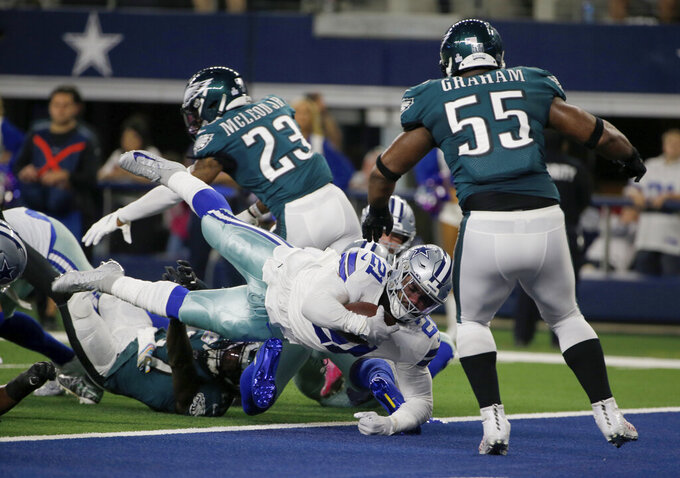 Dallas Cowboys running back Ezekiel Elliott (21) reaches the end zone for a touchdown as Philadelphia Eagles' Brandon Graham (55) looks on the first half of an NFL football game in Arlington, Texas, Sunday, Oct. 20, 2019. (AP Photo/Michael Ainsworth)