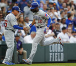 Chicago Cubs third base coach Brian Butterfield, left, congratulates Jason Heyward as he circles the bases after hitting a solo home run off Colorado Rockies starting pitcher Peter Lambert in the second inning of a baseball game Tuesday, June 11, 2019, in Denver. (AP Photo/David Zalubowski)