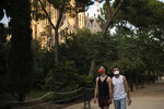 Piotr Grabarczyk and his boyfriend Kamil Pawlik, right, walk in a park near the Sagrada Familia basilica in Barcelona, Spain, Thursday, July 30, 2020. Grabarczyk and Pawlik are starting over in Spain, a country that — unlike Poland — allows same-sex couples the right to marry and adopt children. Like them, many LGBT people are choosing to leave Poland amid rising homophobia promoted by President Andrzej Duda and other right-wing populist politicians in power. (AP Photo/Felipe Dana)