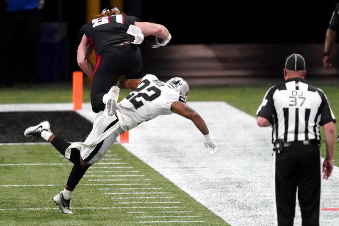 Las Vegas Raiders cornerback Keisean Nixon (22) hits Atlanta Falcons tight end Hayden Hurst (81) during the first half of an NFL football game, Sunday, Nov. 29, 2020, in Atlanta. (AP Photo/John Bazemore)