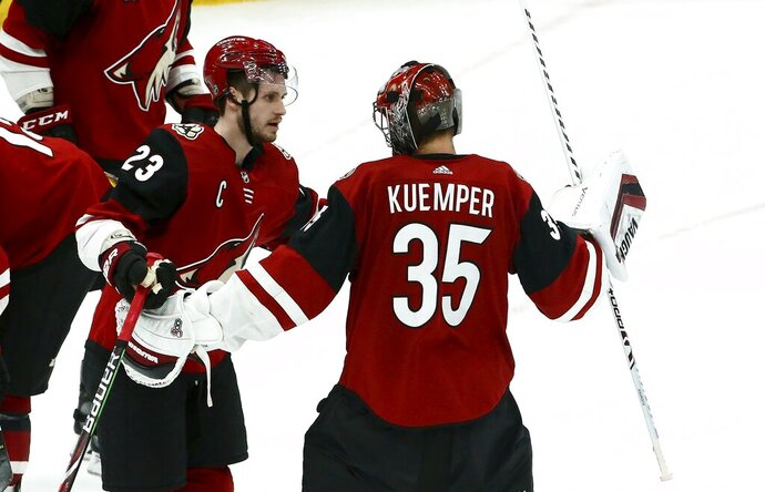 Arizona Coyotes goaltender Darcy Kuemper (35) celebrates his shutout against the Chicago Blackhawks with Coyotes defenseman Oliver Ekman-Larsson (23) as time expires the third period of an NHL hockey game Tuesday, March 26, 2019, in Glendale, Ariz. The Coyotes defeated the Blackhawks 1-0. (AP Photo/Ross D. Franklin)