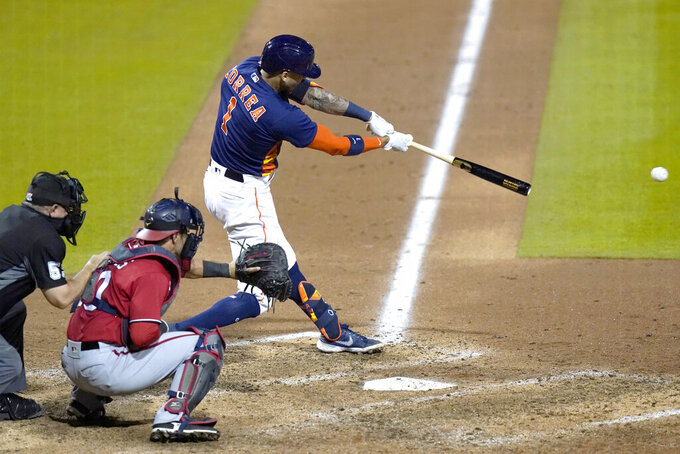 Houston Astros' Carlos Correa (1) hits a single to score Alex Bregman during the fifth inning of a spring training baseball game against the Washington Nationals, Friday, March 19, 2021, in West Palm Beach, Fla. At left is Nationals catcher Yan Gomes (10). (AP Photo/Lynne Sladky)