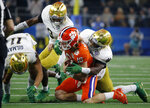 Notre Dame safety Alohi Gilman (11), cornerback Donte Vaughn (8) and linebacker Te'von Coney, right, combine to stop Clemson quarterback Trevor Lawrence (16) after a short run for a first down in the first half of the NCAA Cotton Bowl semi-final playoff football game, Saturday, Dec. 29, 2018, in Arlington, Texas. (AP Photo/Michael Ainsworth)