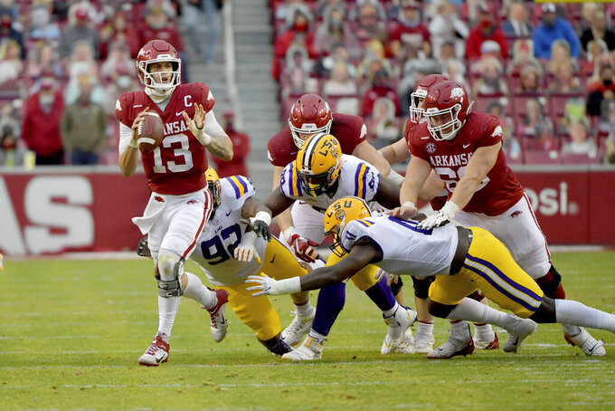 Arkansas quarterback Feleipe Franks (13) tries to get away from LSU defenders as he scrambles out of the pocket during the second half of an NCAA college football game Saturday, Nov. 21, 2020, in Fayetteville, Ark. (AP Photo/Michael Woods)