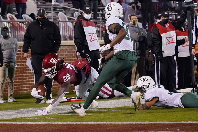 Oklahoma running back Rhamondre Stevenson (29) is stopped short of a touchdown by Baylor cornerback Raleigh Texada, right as cornerback Mark Milton center, moves in during the first half of an NCAA college football game Saturday, Dec. 5, 2020, in Norman, Okla. (AP Photo/Sue Ogrocki)