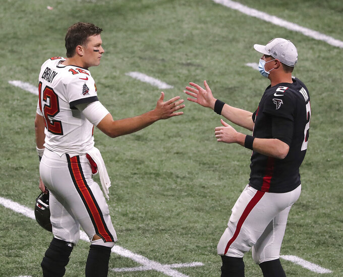 Tampa Bay Buccaneers quarterback Tom Brady, left, and Atlanta Falcons quarterback Matt Ryan greet each other after an NFL football game Sunday, Dec. 20, 2020, in Atlanta. (Curtis Compton/Atlanta Journal-Constitution via AP)