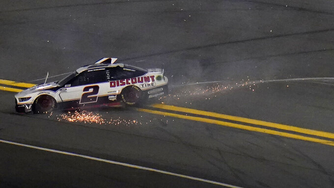 Brad Keselowski (2) slides to the bottom of the track after crashing during the second NASCAR Daytona 500 duel qualifying auto race Friday, Feb. 12, 2021, at the Daytona International Speedway in Daytona Beach, Fla. (AP Photo/Chris O'Meara)