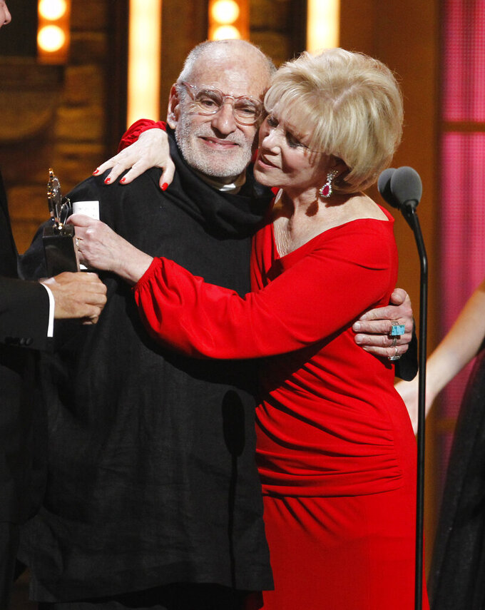 """FILE -This June 12, 2011 file photo shows Larry Kramer, left, and Daryl Roth embracing after they won the Tony Award for Best Revival of a Play for """"The Normal Heart"""" during the 65th annual Tony Awards in New York. Kramer, the playwright whose angry voice and pen raised theatergoers' consciousness about AIDS and roused thousands to militant protests in the early years of the epidemic, died Wednesday, May 27, 2020 in Manhattan of pneumonia. He was 84. (AP Photo/Jeff Christensen, File)"""