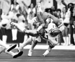 FILE - In this Jan. 9, 1983, file photo, Dallas Cowboys safety Dextor Clinkscale (47) is upended by Tampa Bay Buccaneers offensive tackle Dave Reavis after his interception and 11-yard return during the first quarter of an NFL football playoff game in Irving, Texas. Clinkscale is one of 60 singers--all former NFL players and a couple of current ones--who will participate in the 20th Super Bowl Gospel Celebration at Atlanta Symphony Hall on Thursday night. The choir is set to perform two songs at the sold-out event that's being televised Saturday. (AP Photo/Bill Haber, File)