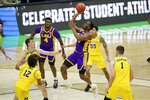 LSU guard Aundre Hyatt, center, drives to the basket over Michigan defenders Franz Wagner, left, Mike Smith (12) and Hunter Dickinson (1) during the first half of a second-round game in the NCAA men's college basketball tournament at Lucas Oil Stadium Monday, March 22, 2021, in Indianapolis. (AP Photo/AJ Mast)