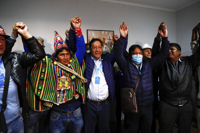 Luis Arce, center, Bolivian presidential candidate for the Movement Towards Socialism Party, MAS, and running mate David Choquehuanca, second right, celebrate during a press conference where they claim victory after general elections in La Paz, Bolivia, Monday, Oct. 19, 2020. (AP Photo/Juan Karita)