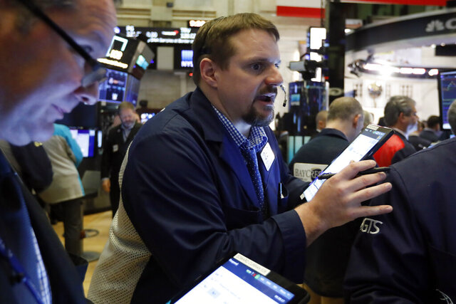 Trader Michael Milano, center, works on the floor of the New York Stock Exchange, Friday, March 6, 2020. Stocks are opening sharply lower on Wall Street and bond yields are sinking to more record lows as investors fear that economic damage from the spreading coronavirus outbreak will be longer than previously thought. (AP Photo/Richard Drew)