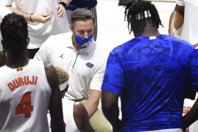 Florida head coach Mike White talks with his team in the first half of an NCAA college basketball game against Army, Wednesday, Dec. 2, 2020, in Uncasville, Conn. (AP Photo/Jessica Hill)