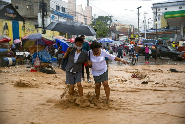 Women walk in a flooded street during the passing of Tropical Storm Laura in Port-au-Prince, Haiti, Sunday, Aug. 23, 2020. Tropical Storm Laura battered the Dominican Republic and Haiti and is heading for a possible hit on the Louisiana coast as a hurricane, along with Tropical Storm Marco. (AP Photo/Dieu Nalio Chery)