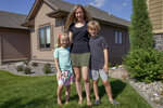 Tara Carlson poses for a photo with her children Kyler, 9, and Alayna, 6, outside their home in Omaha, Neb., Tuesday, July 7, 2020. Carlson pulled her kids out of summer camp at the last minute, losing $300 in deposits. (AP Photo/Nati Harnik)