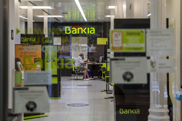 A man sits inside of the Bankia bank in Madrid, Spain, Friday, Sept. 18, 2020. Two of Spain's biggest banks have announced their merger, pushed together by a need to weather tough economic times that likely will cost thousands of jobs. The tie-up between CaixaBank and Bankia will create the largest lender in the country, with assets of more than 664 billion euros ($787 billion). (AP Photo/Manu Fernandez)