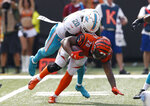 FILE - In this Oct. 7, 2018, file photo, Cincinnati Bengals running back Joe Mixon (28) is tackled by Miami Dolphins free safety Reshad Jones (20) during the second half of an NFL football game in Cincinnati. Jones mysteriously took himself out of last week's win over the New York Jets and watched the second half from the sideline. In the aftermath, coach Adam Gase said communication problems between defensive coordinator Matt Burke and players needed to be addressed. (AP Photo/Gary Landers, File)