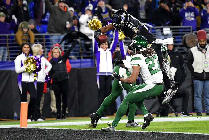 Baltimore Ravens running back Mark Ingram (21) dives over New York Jets free safety Marcus Maye and cornerback Darryl Roberts (27) for a touchdown during the second half of an NFL football game, Thursday, Dec. 12, 2019, in Baltimore. (AP Photo/Nick Wass)