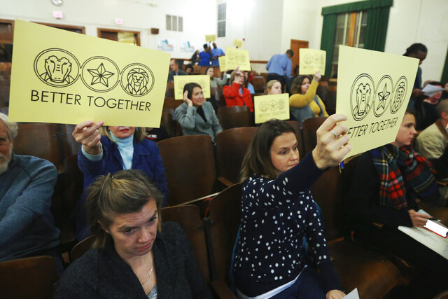 In this Dec. 16, 2019, photo, attendees hold signs during the Richmond School Board's last public hearing on redistricting at Ginter Park Elementary School in Richmond, Va. From New York City to Richmond, sweeping proposals to ease inequities have been scaled back or canceled after encountering a backlash. In Virginia's capital city, the school board approved a plan that reassigned some students but rejected more sweeping proposals that would have diversified Richmond's whitest elementary schools. (AP Photo/Steve Helber)