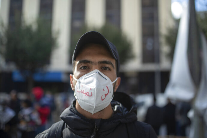 A young man wearing a face mask poses for a portrait during a protest on the tenth anniversary of the uprising that toppled longtime autocrat Ben Ali, during to a national lockdown after a surge in COVID-19 cases, in Tunis, Thursday, Jan. 14, 2021. Writing in Arabic on facemark reads