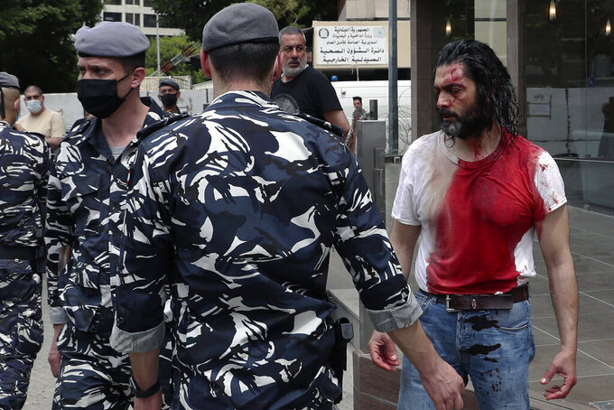 FILE - In this April 19, 2021 file photo, policemen stand guard next to a man in a blood-soaked shirt who was viciously beaten by opponents of Judge Ghada Aoun, during a sit-in outside the Justice Palace in Beirut, Lebanon. A public feud in recent weeks among prosecutors has starkly demonstrated how Lebanon's system of sectarian factions is paralyzing Lebanon's judicial system and snarling attempts to root out corruption. Aoun, a prominent prosecutor says she is trying to go after rampant corruption but her critics say she is only targeting enemies of her ally, the president. (AP Photo/Bilal Hussein, File)