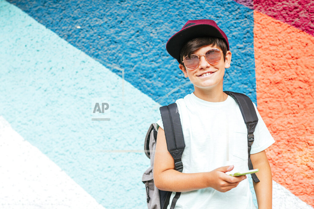 Smiling boy with sunglasses and mobile phone standing in front of wall