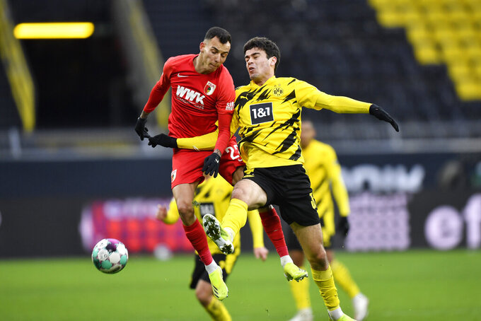 Dortmund's Giovanni Reyna, right, is challenged by Augsburg's Marco Richter during the German Bundesliga soccer match between Borussia Dortmund and FC Augsburg in Dortmund, Germany, Saturday, Jan. 30, 2021. (AP Photo/Martin Meissner, Pool)